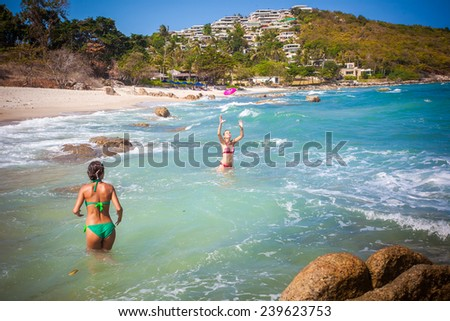 beautiful young woman wearing a green bikini playing  at the beach with her friend on Koh Samui. Thailand - stock photo