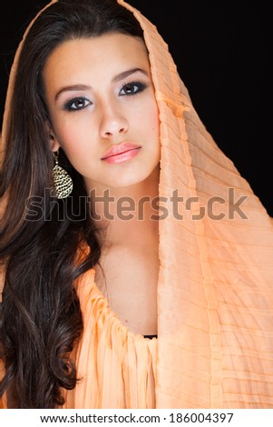 Beautiful young woman wearing a shawl on a black background. - stock photo