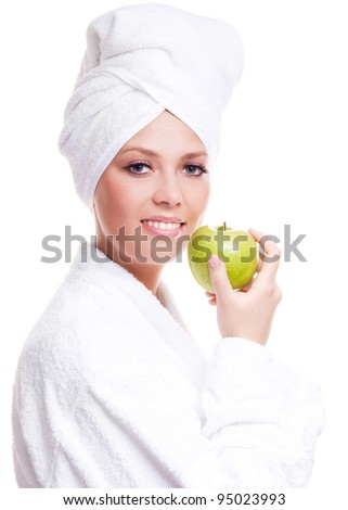 beautiful young woman wearing a towel and a white bathrobe and holding an apple, isolated against white background - stock photo