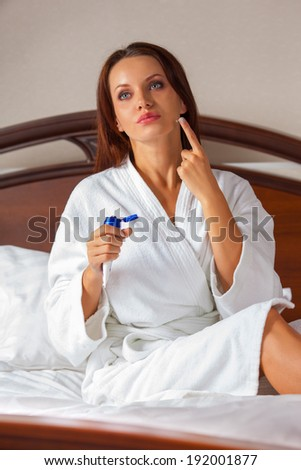 beautiful young woman wearing a white bathrobe and applying body lotion - stock photo