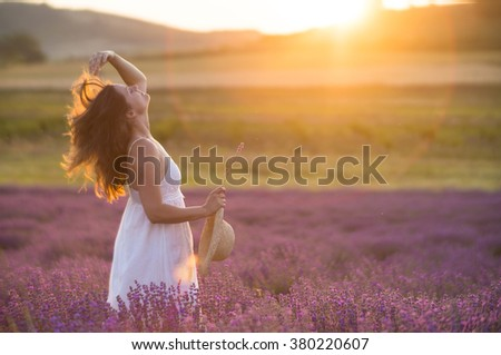 Beautiful young woman wearing a white dress playing with he long hair in a middle of a lavender field under the golden light of sunset. - stock photo