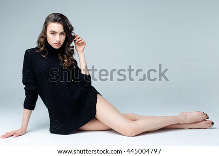 Beautiful young woman wearing black dress on gray background - stock photo