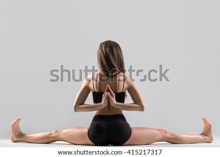 Beautiful young woman wearing black sportswear working out in studio. Fit sporty girl doing advanced yoga, pilates, fitness. Upavishtha Konasana, Wide-Angle Seated Forward Bend posture. Back view - stock photo