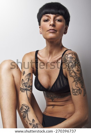 Beautiful young woman wearing black underwear. With black mushroom hair cut, lot of tattoos on her body . Sitting and sexy looking at camera. Developed from RAW. Retouched with special care. - stock photo