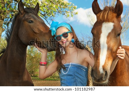 Beautiful young woman wearing blue dress with a horses outdoor. - stock photo
