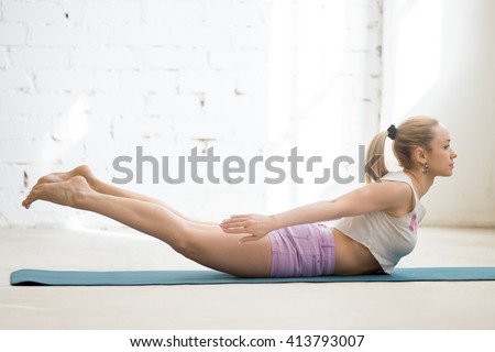 Beautiful young woman wearing casual clothing enjoying yoga indoors. Yogi girl working out in sunny loft interior. Doing Salabhasana (Locust Pose) or Double Leg Kicks exercise. Full length - stock photo