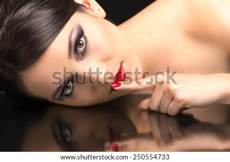 beautiful young woman wearing dark makeup and her reflection in mirror table touching her mouth gesturing shhh - stock photo