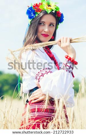 beautiful young woman wearing national ukrainian clothes posing in wheat field - stock photo