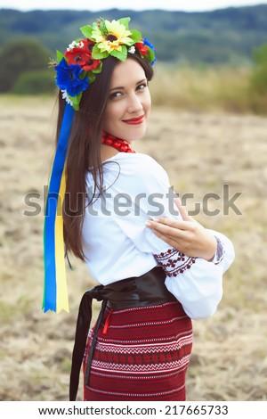 beautiful young woman wearing national ukrainian clothes posing outdoors - stock photo