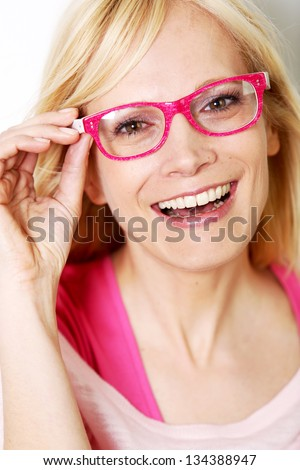 Beautiful young woman wearing pink glasses - stock photo
