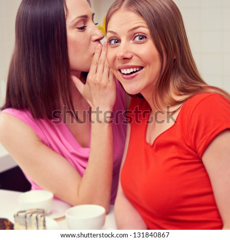 beautiful young woman whispering message to her friend - stock photo