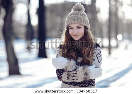 Beautiful Young Woman Winter Portrait at snowy winter day in the park. Happy Caucasian female wintertime season outdoor - stock photo
