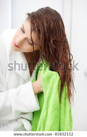 Beautiful young woman wipes her hairs with a towel. - stock photo