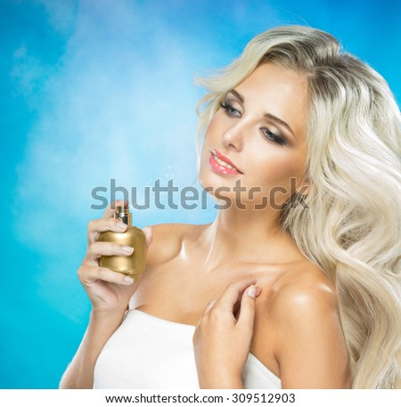Beautiful young woman with a gold bottle of perfume - stock photo
