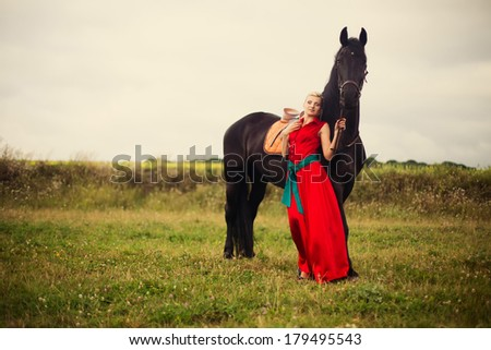 Beautiful young woman with a horse outdoor - stock photo
