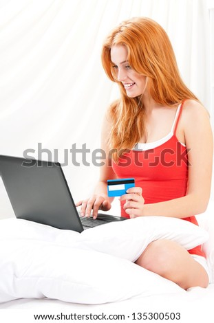 Beautiful young woman with a laptop and credit card, sitting on a bed �¢?? indoors - stock photo