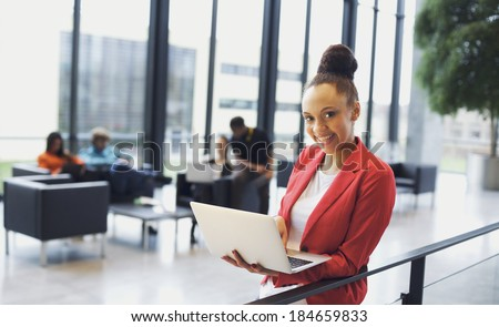 Beautiful young woman with a laptop in modern office. African american businesswoman standing by a railing with people working in background. - stock photo
