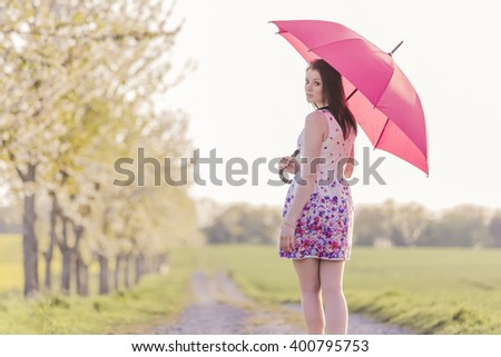 Beautiful young woman with a red umbrella in spring or summer. The weather is changeable between rain and sun. The attractive girl is alone for a walk in a wonderful avenue in nature - stock photo