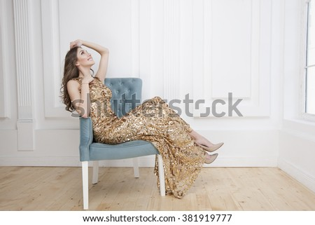 Beautiful young woman with a smile on her face, the girl in a golden long dress - stock photo