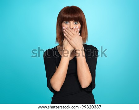 beautiful, young woman, with a surprised face expression, covering her mouth, on blue background - stock photo