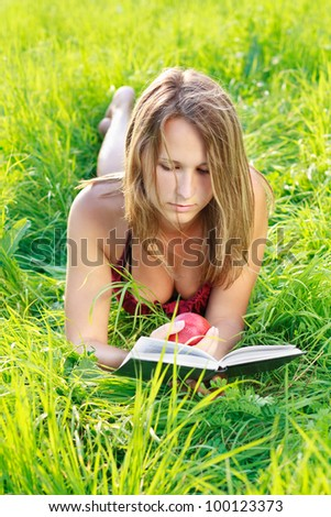 Beautiful young woman with an apple in hand lying on the green grass and reading a book a sunny day against a background of green nature - stock photo