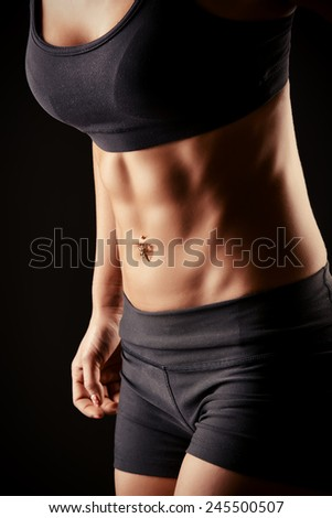Beautiful young woman with an athletic physique. Fitness sports. Healthcare, bodycare. Black background. - stock photo