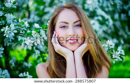 beautiful young woman with apple trees in the park in summertime - stock photo