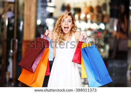 Beautiful young woman with bags in shopping center - stock photo
