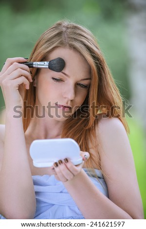 Beautiful young woman with bare shoulders eyes colors and mirror, against green of summer park. - stock photo