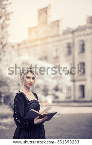 Beautiful young woman with blond hair in black medieval dress reading a book in the park against the backdrop of a medieval castle - stock photo