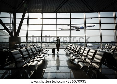 beautiful young woman with blond short hair with a suitcase at the airport and waiting for her flight and airplane taking off - stock photo