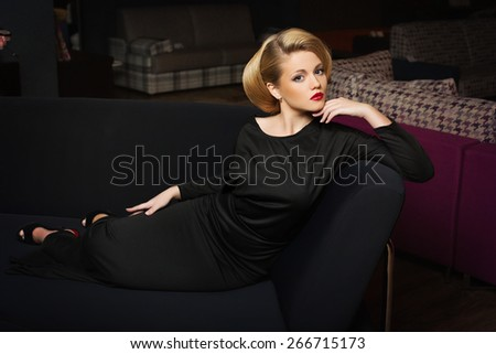 Beautiful young woman with blonde hair wearing black evening dress lying on grey sofa - stock photo