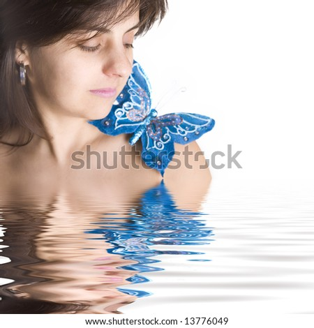 beautiful young woman with blue butterfly in her naked shoulder - focus on the eye - stock photo