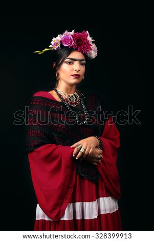Beautiful young woman with bright make up and flowers in hair looking like Frida Kahlo. Over black background. Close up portrait. Studio shot - stock photo