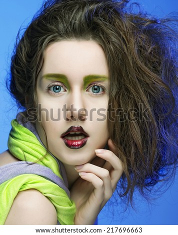 beautiful young woman with bright make-up over blue background - stock photo