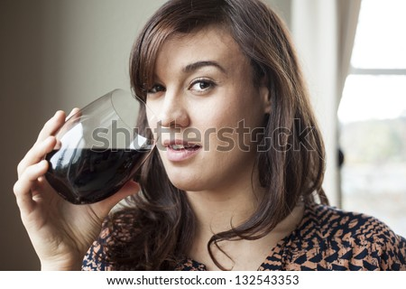 Beautiful young woman with brown hair drinking red wine. - stock photo