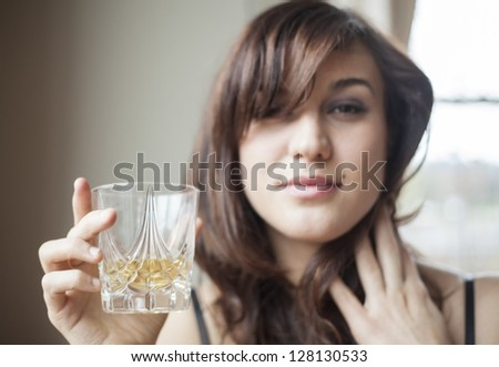 Beautiful young woman with brown hair in lingerie drinking a tumbler of Scotch. - stock photo