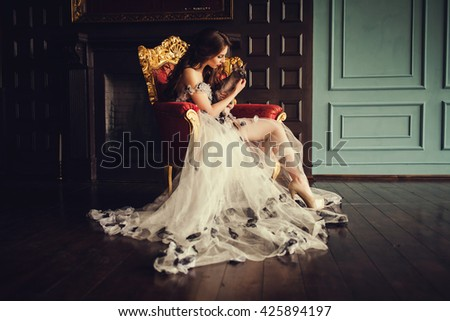 Beautiful young woman with cat sitting in a trendy dress - stock photo