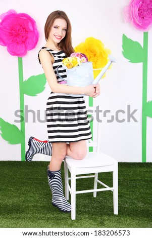 Beautiful young woman with chair on decorative background - stock photo