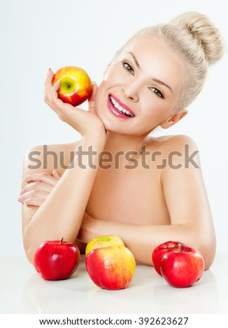 Beautiful Young Woman with Clean Fresh Skin. Beautiful smile, straight teeth. Perfect Skin. Professional Makeup. A smiling woman with apples. - stock photo