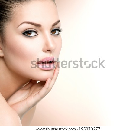 Beautiful Young Woman with Clean Fresh Skin close up isolated on white. Beauty Portrait. Spa Woman Smiling and touching her skin. Perfect Fresh Skin. Pure Beauty Model. Youth and Skin Care Concept  - stock photo
