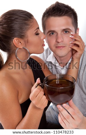Beautiful young woman with closed eyes holding a cup of tea and touching the cheek of young man - stock photo