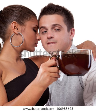 Beautiful young woman with closed eyes holding a cup of tea and touching with her nose the cheek of young man - stock photo