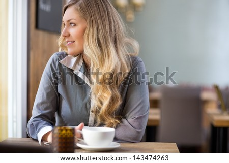 Beautiful young woman with coffee cup looking away at coffeeshop - stock photo