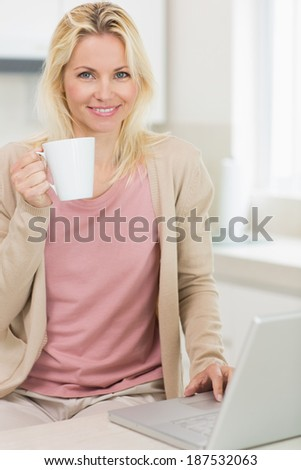 Beautiful young woman with coffee cup using laptop in the kitchen at home - stock photo