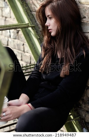 beautiful young woman with coffee sitting on the street - stock photo