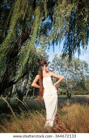 Beautiful young woman with creative fashion hairstyle. Spanish flamenco hairstyle. Creative makeup. Shooting outdoor.  - stock photo