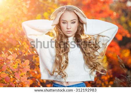 beautiful young woman with curly hair against a background of red and yellow autumn leaves. - stock photo