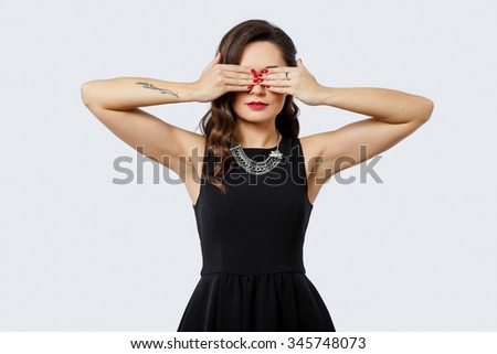 Beautiful young woman, with curly hair and tattoo on her arm, wearing in black dress, close her eyes by her hands on white background, in studio, waist up - stock photo