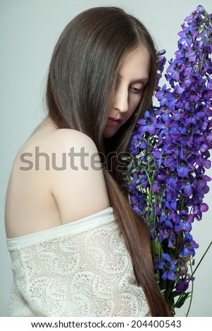Beautiful young woman with delicate wildflowers - stock photo